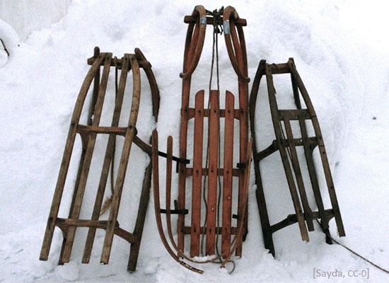 Farbfoto: 3 an Schneehaufen angelehnte Schlitten aus den 50ern - 2019