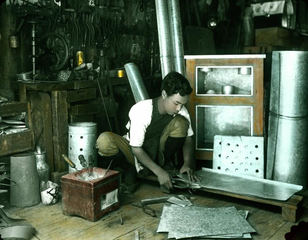 koloriertes Foto: asiatischer Arbeiter schneidet Bleche zurecht