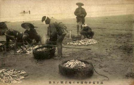 alte Fotokarte: Männer sortieren ihren Fischfang am Strand